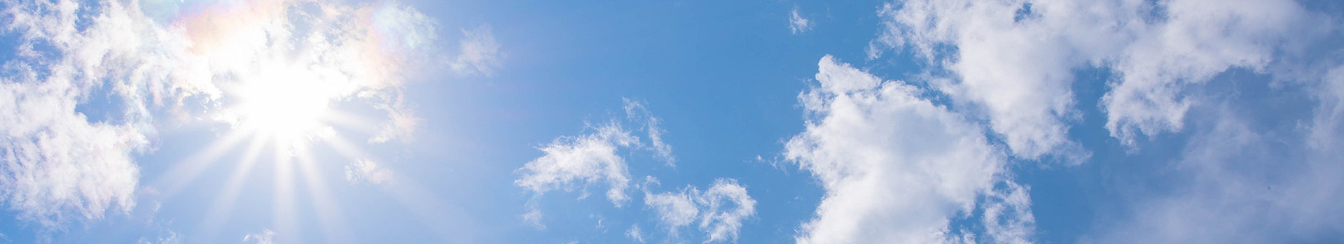 Sun and scattered clouds in a blue sky